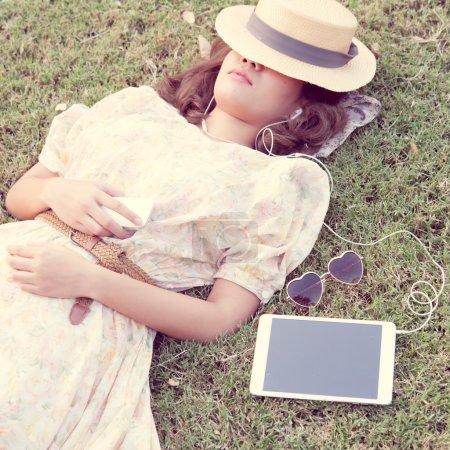 Vintage Girl sleep in park listen music via small talk