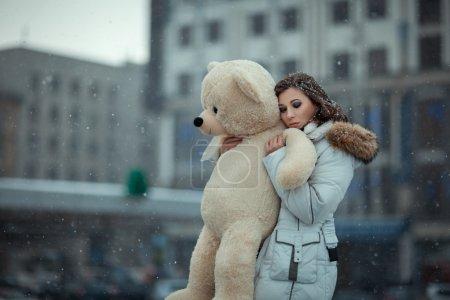 Photo pour Fille en hiver pendant les chutes de neige est dans la ville. Elle caresse l'ours jouet, les yeux fermés et un visage triste. Photo avec ouverture ouverte et mise au point douce. Photo tonique . - image libre de droit