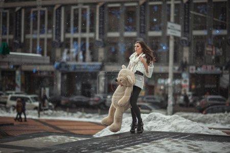 Photo pour La fille avec un ours jouet dans la main vaut la peine dans la ville. Photo prise avec l'ouverture ouverte. Le fond est flou et ne peut pas être lu. Photo tonique . - image libre de droit