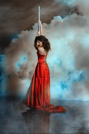 Girl shrouded in smoke holding on to pole dance.