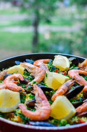 Photo for Close up fresh juicy prepared classic spanish dish paella with seafood, blueshell mussels, shrimps, rice with saffron spice, vegetables, tomatoes, smoked sausages and peaces of lemon and parsley over it in a frying pan. - Royalty Free Image