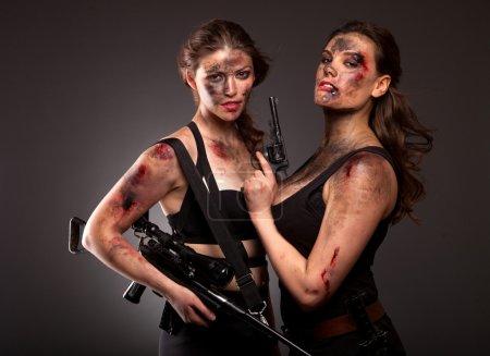 Photo pour Armés de tueurs féminins forts agressifs avec arme - image libre de droit