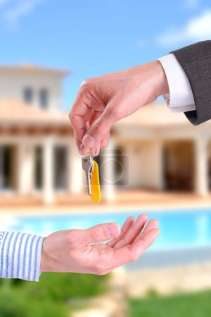 Commercial agent giving keys to customer vertical composition