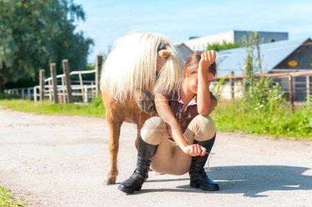 Lets play! Teenage cheerful girl with playful shetland pony.