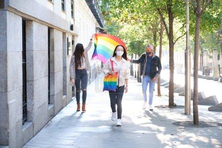 Photo pour Groupe de trois amis portant un masque facial agitant le drapeau LGBT dans la rue. Fête de la fierté LGBT en période de pandémie. - image libre de droit