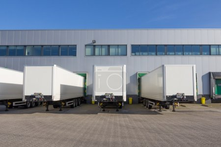 Photo for Three white trailers waitng to be loaded at docking stations of a distribution center - Royalty Free Image