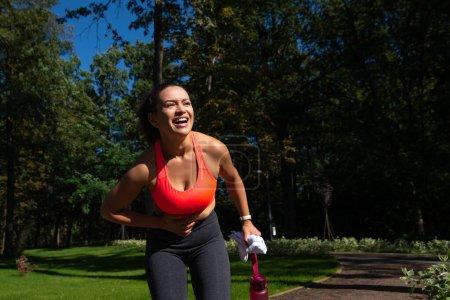 Brünette Läuferin mit Magenkrämpfen nach dem Laufen im Freien. Sportverletzung