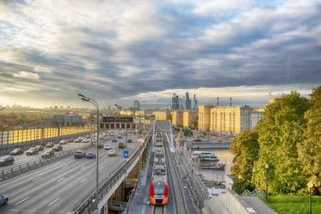 The skyscrapers, the Third Ring Road and the ES2G Lastochka (Swallow) trains on the Moscow Central Circle line at sunset. Time-lapse. Moscow. Russia