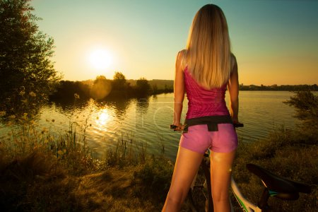 Photo for Close-up of rear view of a pretty woman on bicycle relaxing at Sunset. Active Leisure Concept. Healthy lifestyle. - Royalty Free Image
