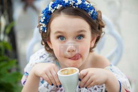 Portrait of little girl in a floral dress drinking coffee