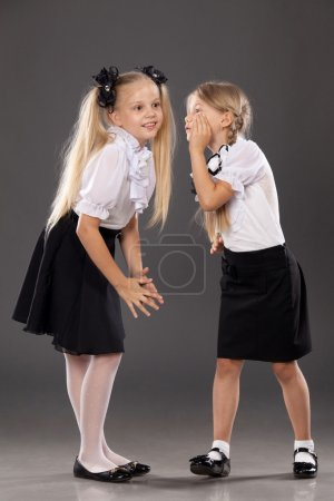 Two little schoolgirls speaking and sharing secrets