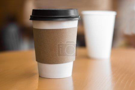 Photo pour Two paper coffee cups on wooden table - image libre de droit