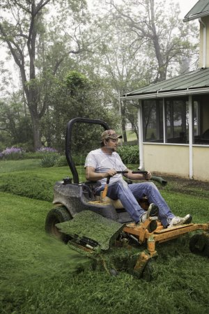 Man cutting grass on riding lawnmower