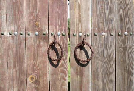 Metal old rusty round handle on wooden doors