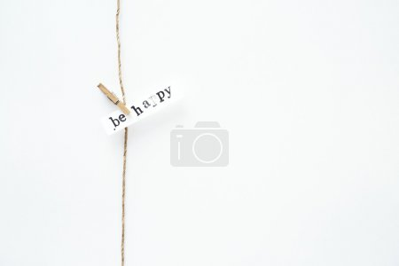 Photo for Tiny simple garland with sign over white wall BE HAPPY. Motivational hipster quote. Scandinavian interior. With place for text. - Royalty Free Image