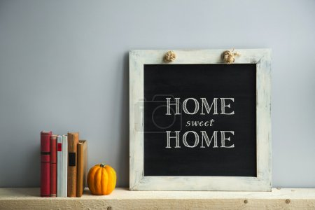 Photo for Chalkboard frame on the grey wall with books and pumpkin HOME SWEET HOME - Royalty Free Image