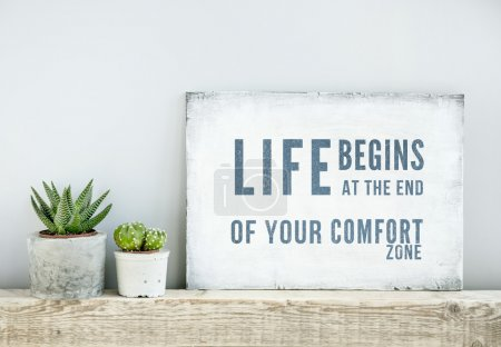 Foto de Motivational poster quote LIFE BEGINS AT THE END OF COMFORT ZONE. scandinavian or american style room interior. - Imagen libre de derechos