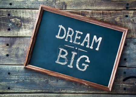 Hand drawn chalkboard sign DREAM BIG over old wooden table backg
