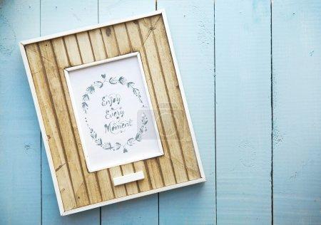 Photo pour Ancien cadre rétro sur fond de bois bleu vintage avec lettrage Enjoy Every Moment - image libre de droit