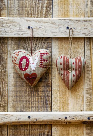 Photo for Two hearts hanging over rustic wooden background. Symbol of love. Gfeeting card for wedding, engagement or Valentine's day - Royalty Free Image