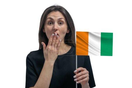 Photo pour Heureuse jeune femme blanche tenant le drapeau de la Côte d'Ivoire et couvrant sa bouche avec sa main isolée sur fond blanc. - image libre de droit