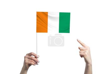 Photo pour Une belle main féminine tient un drapeau de Côte d'Ivoire sur lequel elle montre le doigt de son autre main, isolée sur fond blanc. - image libre de droit
