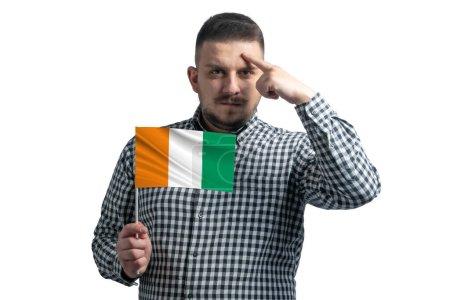 Photo pour Blanc tenant un drapeau de Côte d'Ivoire et un doigt touche le temple sur la tête isolé sur un fond blanc. - image libre de droit