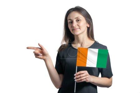 Photo pour Heureuse jeune femme blanche tenant pavillon Côte d'Ivoire et pointant vers la gauche isolée sur fond blanc. - image libre de droit
