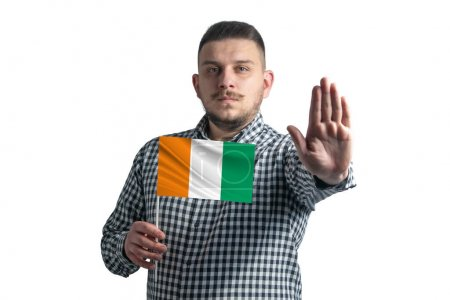 Photo pour Blanc tenant un drapeau de Côte d'Ivoire et avec un visage sérieux montre un panneau d'arrêt de main isolé sur un fond blanc. - image libre de droit