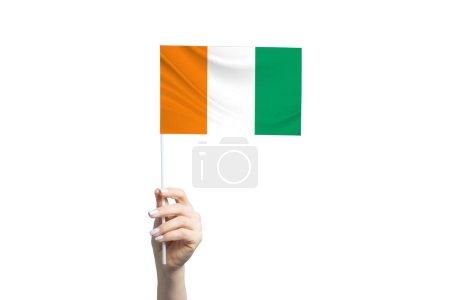 Photo pour Belle main féminine tenant le drapeau C te d'Ivoire, isolée sur fond blanc. - image libre de droit