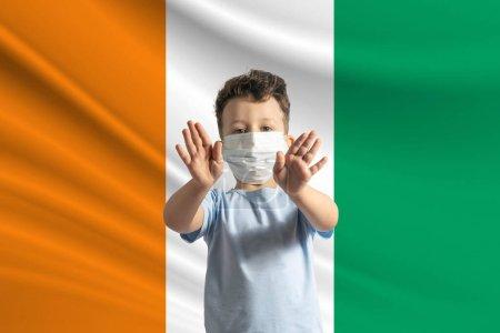Photo pour Petit garçon blanc dans un masque de protection sur le fond du drapeau de la Côte d'Ivoire Fait un stop signe avec ses mains, rester à la maison Côte d'Ivoire. - image libre de droit