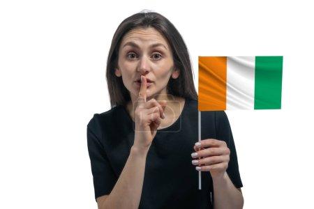 Photo pour Heureuse jeune femme blanche tenant le drapeau de la Côte d'Ivoire et tenant un doigt sur ses lèvres isolées sur un fond blanc. - image libre de droit