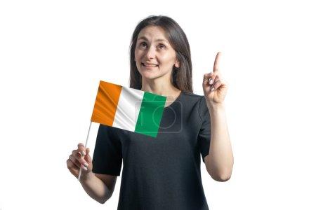 Photo pour Heureuse jeune femme blanche tenant le drapeau de Côte d'Ivoire et pointant les pouces vers le haut isolée sur un fond blanc. - image libre de droit