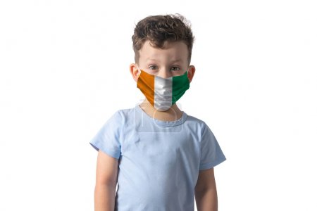 Photo pour Respirator with flag of Cote d'Ivoire White boy puts on medical face mask isolated on white background. - image libre de droit