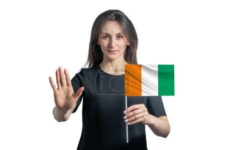 Photo pour Joyeux jeune femme blanche tenant le drapeau de la Côte d'Ivoire et avec un visage sérieux montre un panneau d'arrêt de main isolé sur un fond blanc. - image libre de droit