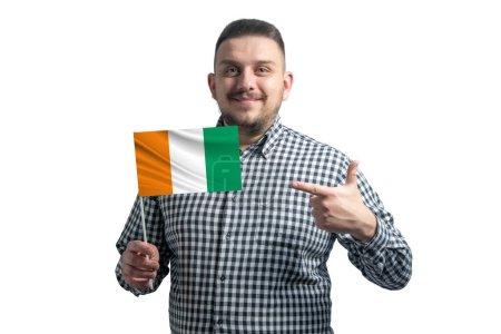 Photo pour Blanc tenant un drapeau de Côte d'Ivoire et pointant du doigt l'autre main sur le drapeau isolé sur fond blanc. - image libre de droit