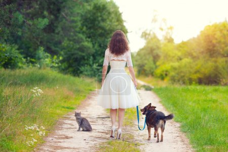Bride with dog and cat on the rural road