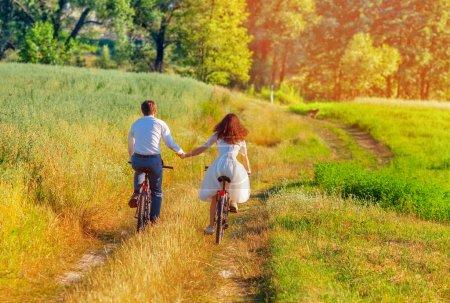 Photo pour Mariée et marié équitation vélos dans la prairie d'été - image libre de droit