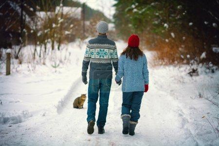Photo pour Jeune couple amoureux se tenant la main sur la route enneigée du village - image libre de droit