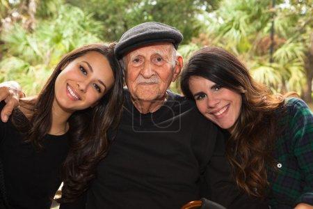 Photo pour Personnes âgées quatre-vingt plus homme ans avec petites-filles dans un décor extérieur. - image libre de droit