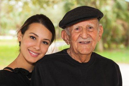 Photo pour Personnes âgées quatre-vingt plus homme ans avec petite fille dans un décor extérieur. - image libre de droit