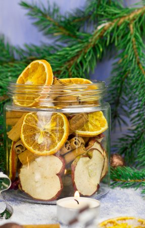 Christmas decoration. Fir tree, snow, candles, metal molds for Christmas cookies and jar with dried oranges, dried apples, cinnamon (selective focus)