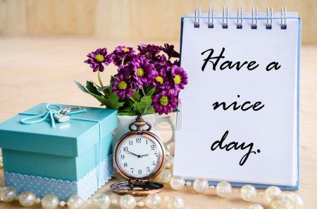 Photo pour Passez une bonne journée. Journal ouvert, montre de poche, boîte cadeau et fleur sur fond en bois dn . - image libre de droit