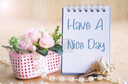 Photo pour Passez une bonne journée. Sur le journal avec tasse de fleurs sur fond en bois . - image libre de droit