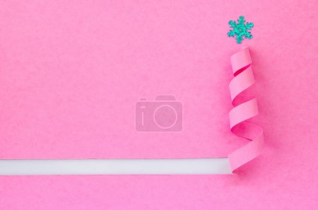 Handmade Christmas tree cut out from pink paper.