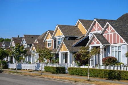 Photo pour Une rangée de maisons neuves à Richmond, Colombie-Britannique, Canada. Verges avant des maisons et de la rue avec des arbres et des buissons . - image libre de droit