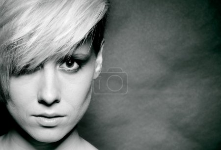 Girl with a short stylish haircut on a dark background