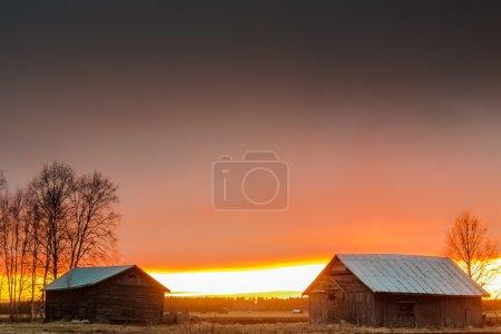 Last Rays Of Sun Behind The Barn Houses
