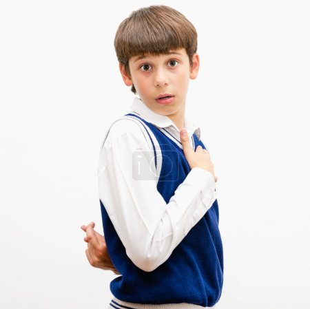 Photo for Portrait of a dark-haired boy on a gray background. He cheats. - Royalty Free Image