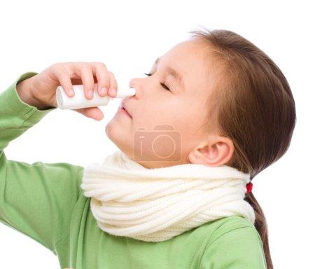 Cute girl spraying her nose